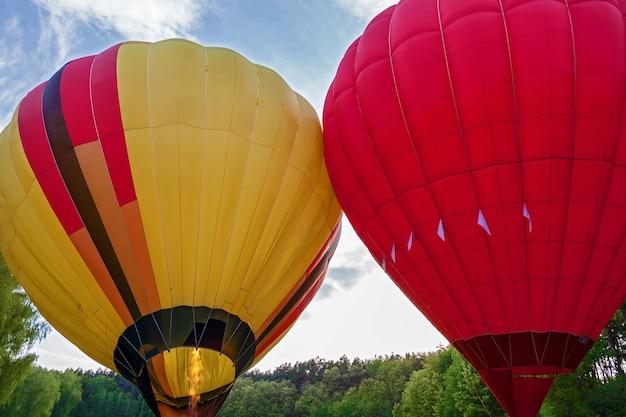 Ein ballon mit einem korb, der mit heißer luft gefüllt und flugbereit ist. vorbereitung eines ballons für den flug. fest der ballons