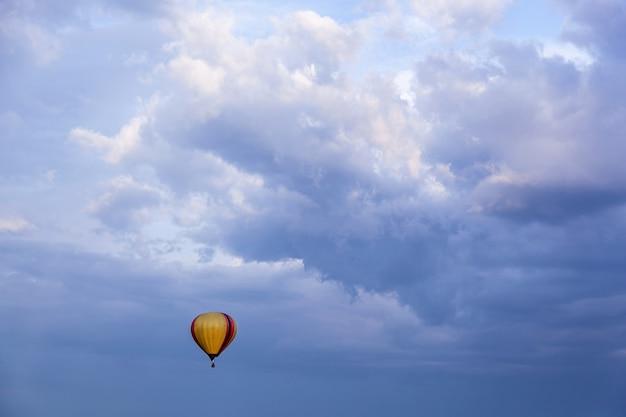 Ein ballon mit einem korb voller heißer luft fliegt in den blauen himmel ein luftballon in den blauen himmel