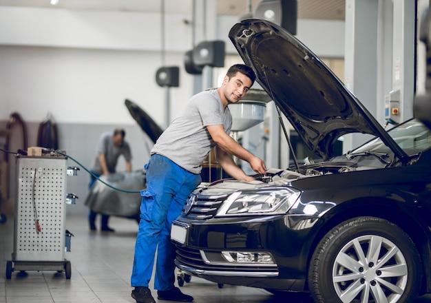 Ein bankier, der den motor eines autos repariert