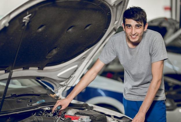 Ein bankkollege repariert den motor eines autos