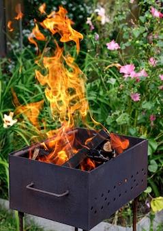 Ein barbecue im freien. lagerfeuer mit holz auf einem hintergrund von blumen.