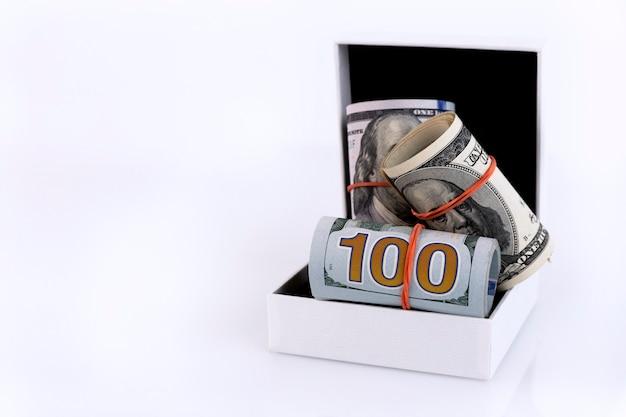 Ein bargeldgeschenk in form von amerikanischem geld rollt in einer weißen geschenkbox