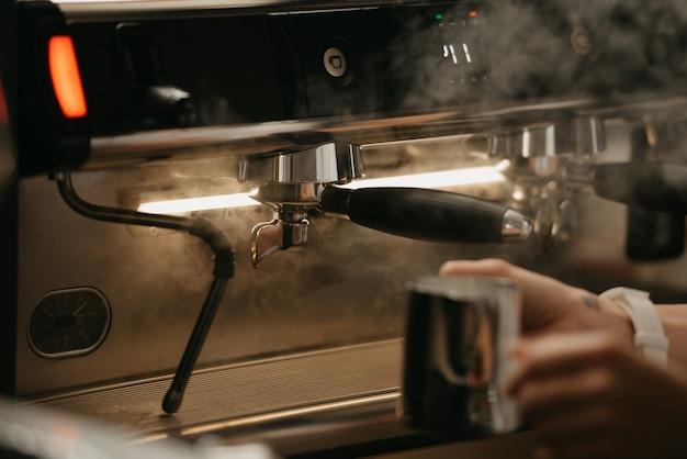 Ein barista, der sich darauf vorbereitet, einen metallbecher mit dampf in einer professionellen espressomaschine zu spülen