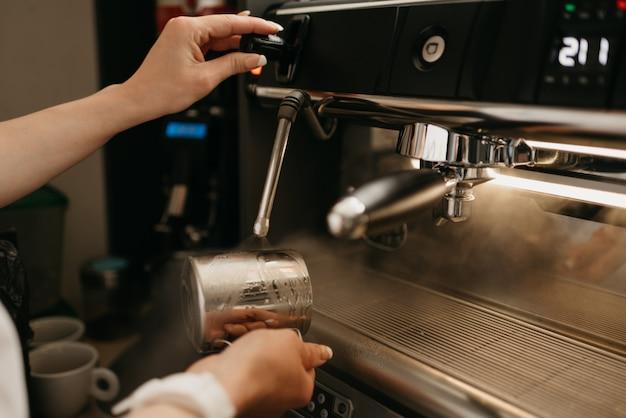 Ein barista trägt eine weiße schürze und spült einen metallbecher mit dampf in einer professionellen espressomaschine