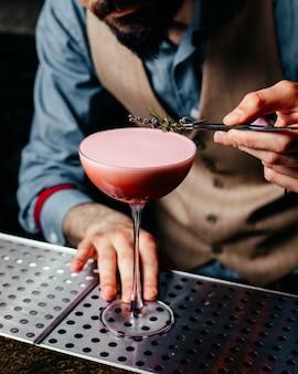 Ein barkeeper mit vorderansicht, der einen cocktail auf dem saftgetränkcocktail des barschreibtischs vorbereitet
