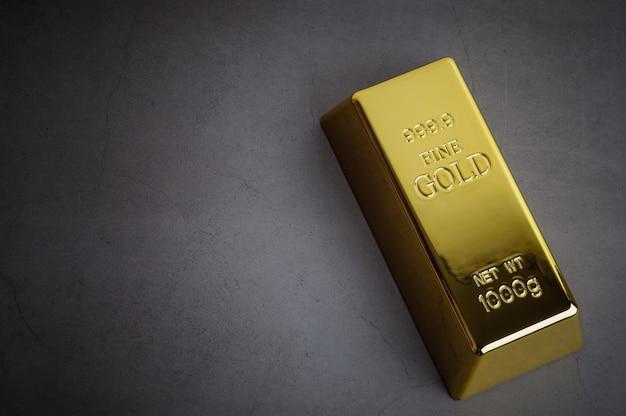 Ein barren aus goldmetallbarren aus reinem glänzendem diagonal auf einem grauen strukturierten hintergrund.