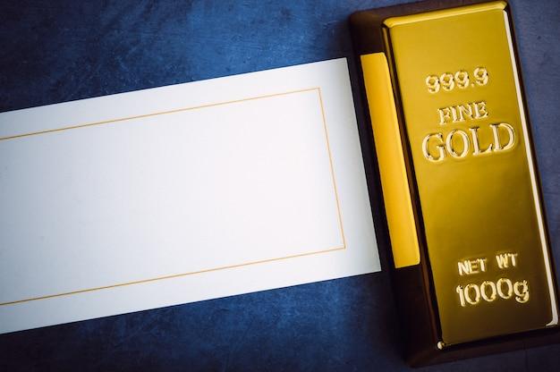 Ein barren aus goldmetallbarren von reinem brillant, diagonal auf einem blau strukturierten hintergrund angeordnet