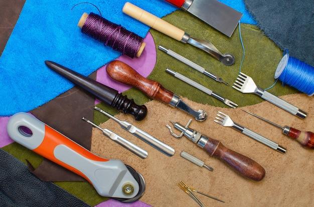 Ein bastelwerkzeug für die arbeit mit leder. entfaltet auf farbigen lederpatches. nahaufnahme