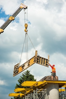 Ein bauarbeiter auf betonsäulen entfernt schalung von einem kranhaken auf einer baustelle