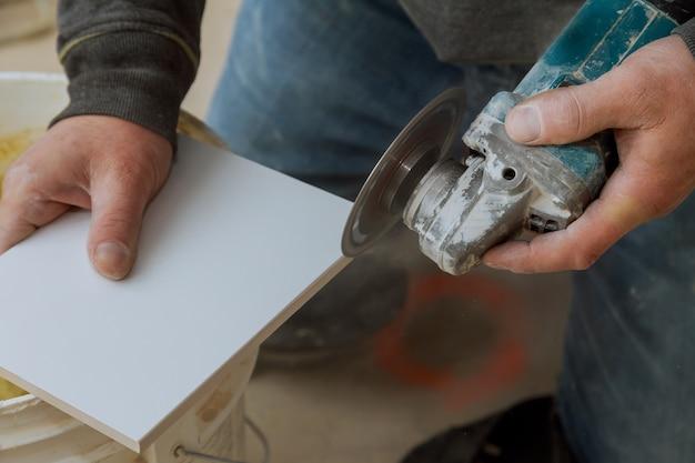 Ein bauarbeiter, der eine fliese unter verwendung einer mühle schneidet
