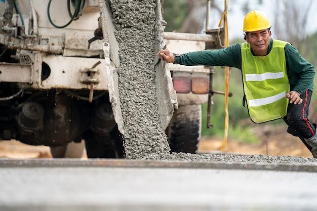 Ein bauarbeiter, der einen nassen beton an der straßenbaustelle gießt