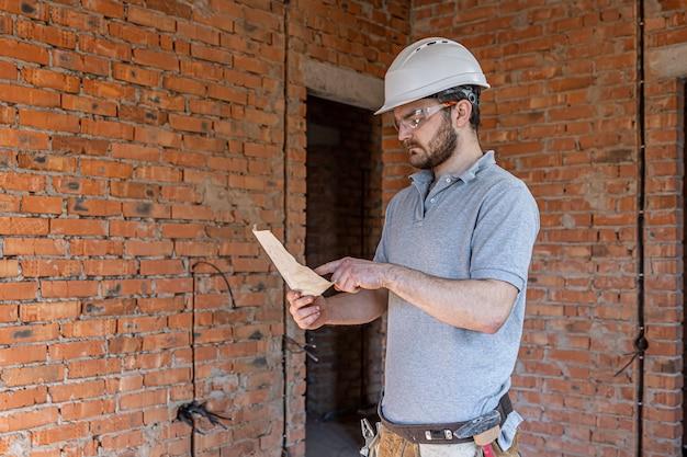 Ein bauarbeiter in arbeitskleidung begutachtet eine bauzeichnung auf einer baustelle.