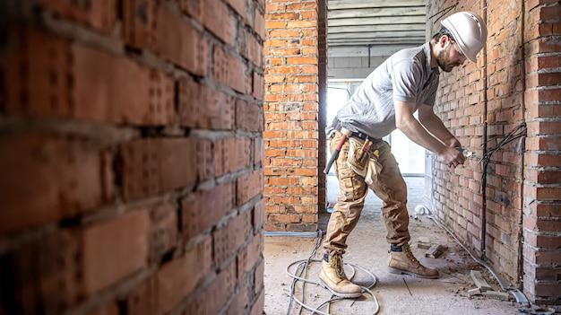 Ein bauelektriker schneidet bei einer reparatur ein spannungskabel durch