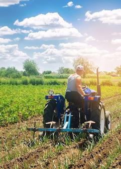 Ein bauer auf einem traktor pflügt ein feld.