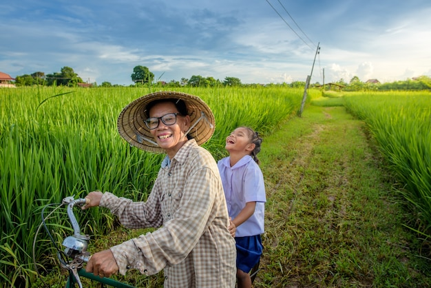 Ein bauer mit mädchen, das einen vietnamesischen hut trägt