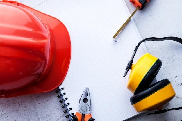 Ein bauhelm ist ein symbol für sicherheit am arbeitsplatz. werkzeugset. sicherheitskonzept tiefenschärfe.
