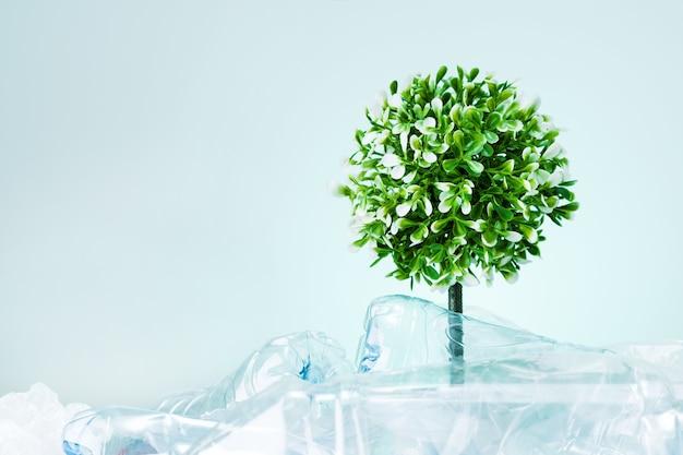 Ein baum, der aus einer müllkippe aus flaschenplastik auf mintfarbenem hintergrund mit kopierraum wächst. speichern sie das erdökologiekonzept.