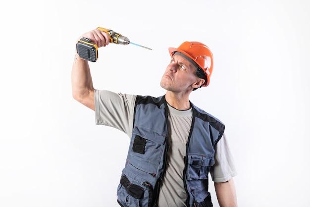 Ein baumeister in einem helm, der versucht, sich mit einem bohrschrauber das auge zu bohren. für jeden zweck.