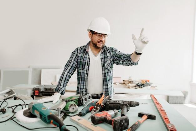 Ein baumeister in einem schutzhelm mit werkzeugen hob bei reparaturen die hand nach oben