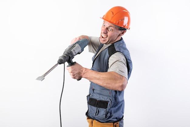 Ein baumeister mit einem lustigen ausdruck, in einem helm, mit einem bohrer in den händen. für jeden zweck.