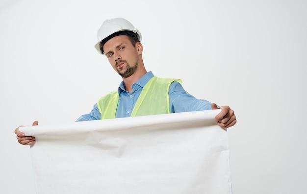 Ein baumeister mit einem plan in den händen eines weißen schutzhelms aus papier.