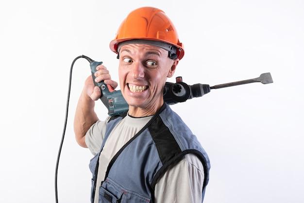 Ein baumeister mit lustigem gesichtsausdruck, im helm, mit einem bohrer auf der schulter.für jeden zweck.
