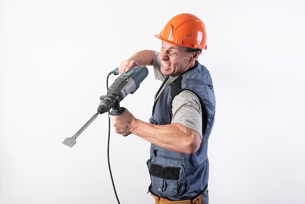 Ein baumeister mit lustigem gesichtsausdruck, in einem helm, mit einem bohrer. für jeden zweck.