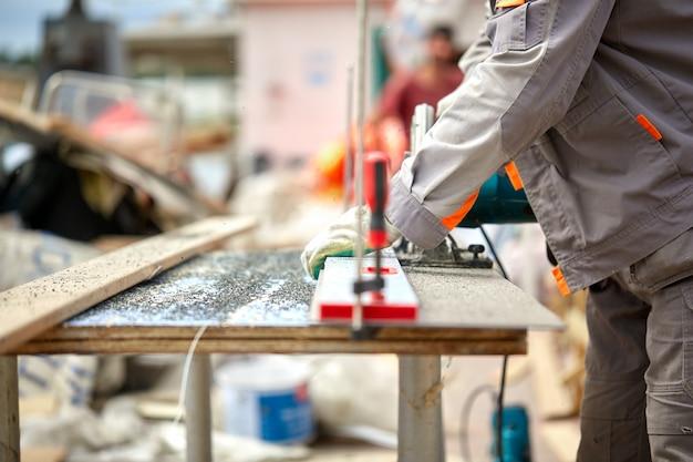 Ein bauunternehmer, der mit einer schneckengetriebenen handkreissäge bretter und plastik schneidet. bau, eigene werkstatt, einstellung eines arbeitsvertrags für das schneiden von holz.