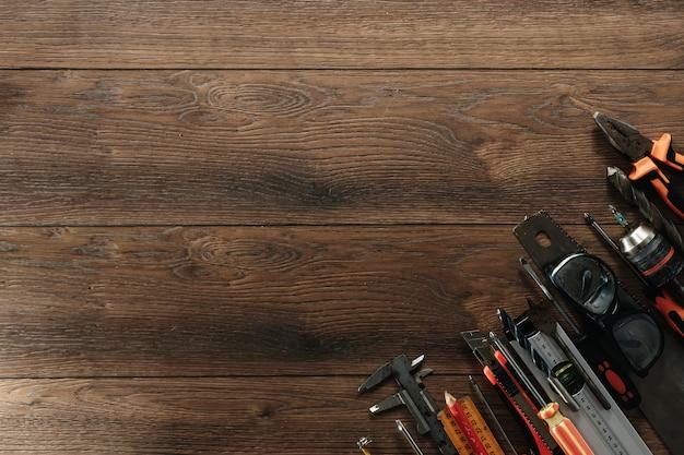Ein bauwerkzeug auf einem braunen hölzernen. sicht von oben. bild, bildschirmschoner. bau, reparatur, bau, produktion,. copyspace.