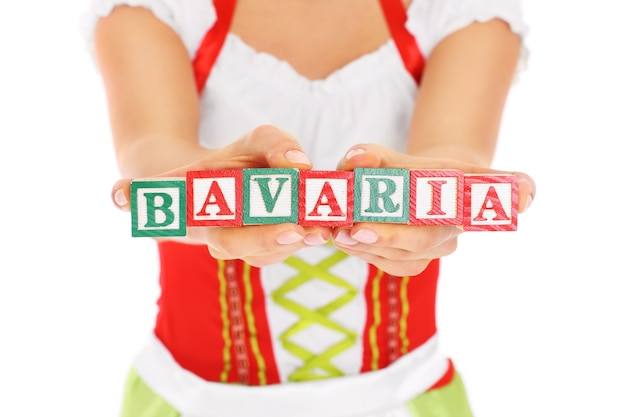 Ein bayerisches mädchen, das holzklötze mit bayern auf weißem hintergrund hält