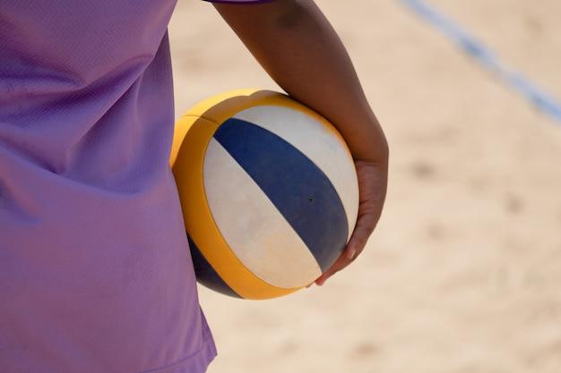 Ein beachvolleyball-athlet, der beachvolleyball in der hand hält