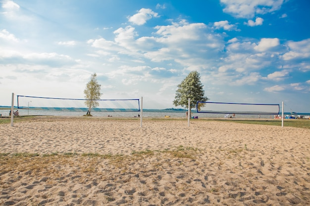 Ein beachvolleyballnetz an einem schönen sonnigen tag. komplett mit sandstrand und meer