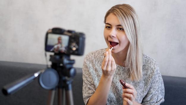 Ein beauty-blogger oder video-blogger erklärt und zeigt abonnenten, wie man make-up macht. junge frau malt lippen