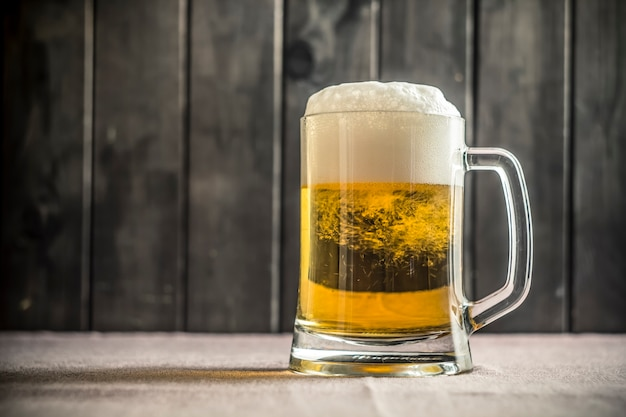 Ein becher frisches bier auf dem tisch der kneipe.