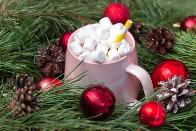 Ein becher mit marshmallow in einem ast eines tannenbaums mit spielzeugkugeln weihnachtsdekorationen des neuen jahres