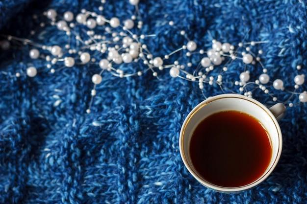 Ein becher tee auf einem blauen strickhintergrund