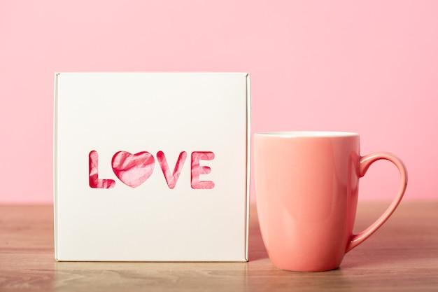 Ein becher und eine geschenkverpackung für einen geliebten menschen. valentinstag konzept. banner.