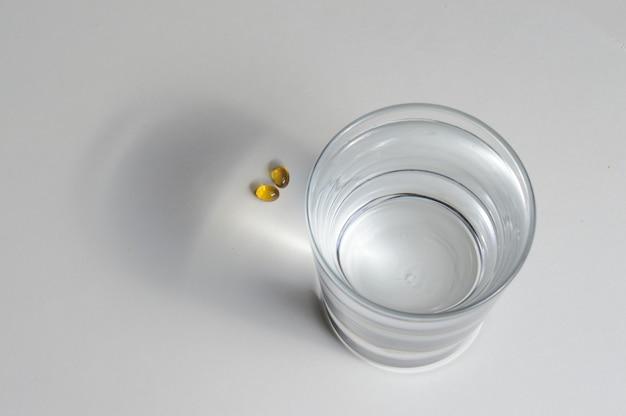 Ein becherglas und zwei gelbe tabletten mit vitaminen. nahaufnahme.