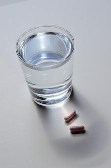 Ein becherglas und zwei rosa kapseln mit vitaminen. nahaufnahme.