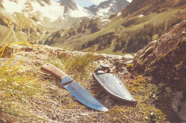 Ein bergmann-messer und eine lederscheide wurden ausgestellt. reiseset für wanderungen in der natur
