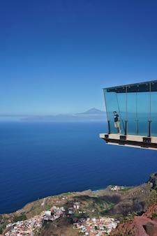 Ein besucher stützt sich an einem sonnigen sommertag auf das glas des mirador de abrante in la gomera, kanarische inseln, spanien. el teide, der höchste berg spaniens, ist im hintergrund zu sehen.
