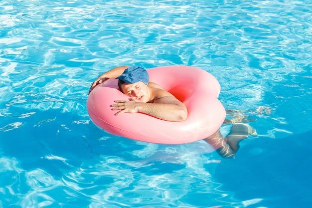 Ein betrunkener mann schwimmt auf aufblasbaren kreis im pool. reise eines russischen touristen