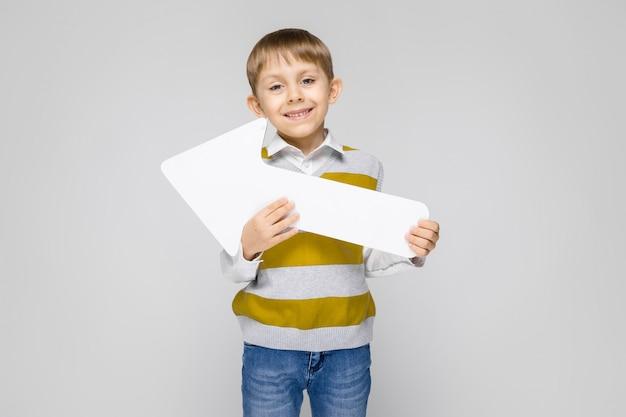 Ein bezaubernder junge in einem weißen hemd, einem gestreiften trägershirt und einer hellen jeans steht auf einem grau. der junge hält einen weißen pfeil in seinen händen