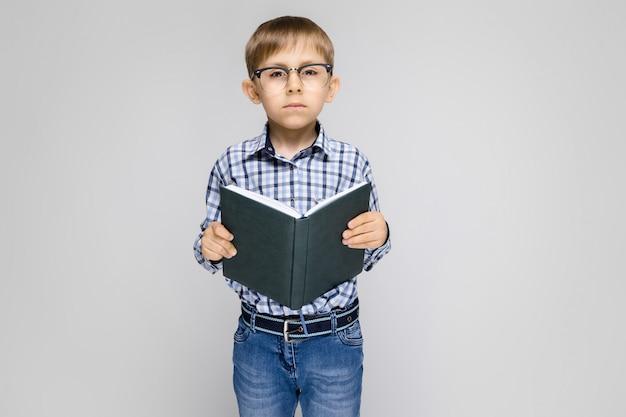 Ein bezaubernder junge mit einem eingelegten hemd und hellen jeans steht auf einem grau. der junge hält ein buch in den händen. junge mit brille