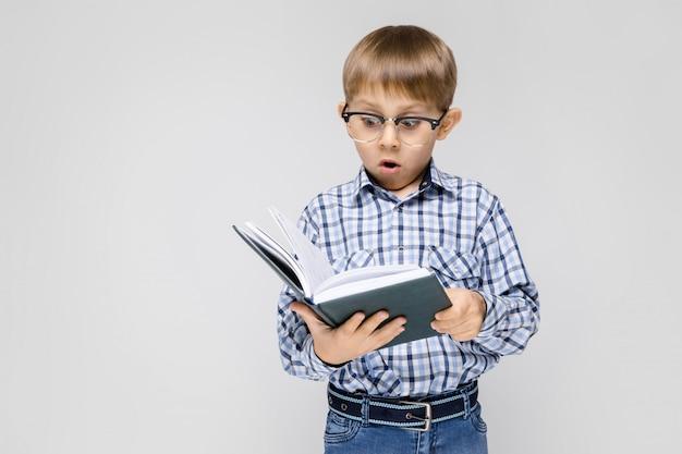 Ein bezaubernder junge mit einem eingelegten hemd und hellen jeans steht auf einem grauen hintergrund. der junge hält ein buch in den händen. junge mit brille