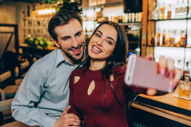 Ein bild, auf dem ein mädchen mit ihrem freund ein selfie macht. sie lächeln und schauen in die kamera. dieses paar ist nett und sehr nett.