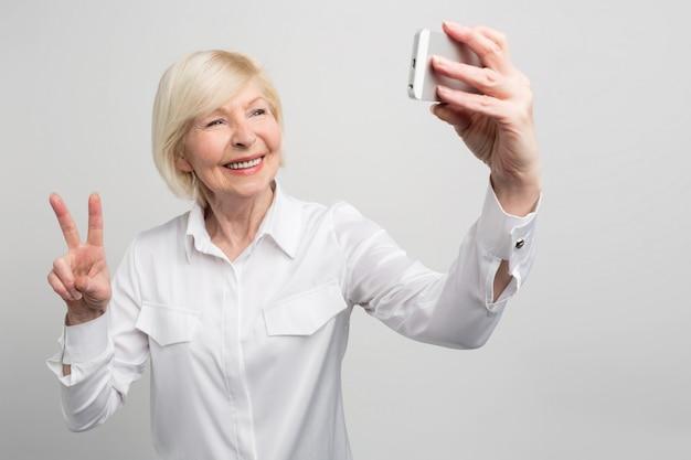 Ein bild aus einem anderen blickwinkel, in dem oma ein selfie macht. sie weiß alles über jugendtrends und nutzt sie überall. sie ist eine sehr moderne alte frau.