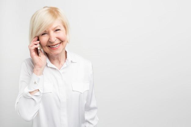 Ein bild der alten dame mit neuem telefon. sie testet es gerne. dieses telefon ist ihr favorit.