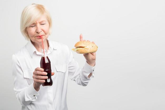 Ein bild der alten frau, die coca cola schmeckt und einen burger isst. sie mag keinen gesunden lebensstil. sie isst lieber lecker, aber dick und schlecht.