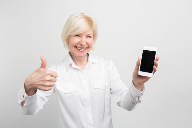 Ein bild der reifen frau mit neuem smartphone. sie hat es getestet und zugegeben, dass dieses telefon gut ist. deshalb zeigt sie einen großen daumen hoch.